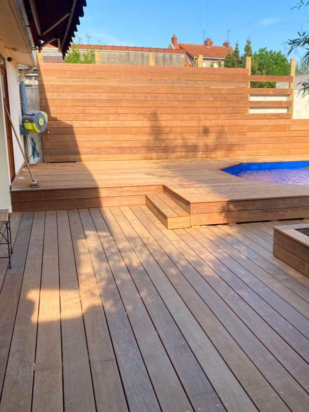 Les margelles sont intégrées à la terrasse, le bardage bois du mur crée une continuité et une cohérence qui donnent un aspect moderne et épuré.