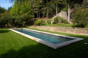 La margelle en pierre naturelle et la couleur de l'eau donnent un aspect bassin traditionnel à cette piscine contemporaine.