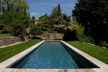 Posé au milieu d'un gazon parfaitement entretenu, ce bassin de nage est comme un grand tapis d'eau qui apporte autant par le plaisir de la nage que celui de la contemplation et apporte un esprit zen à la maison.