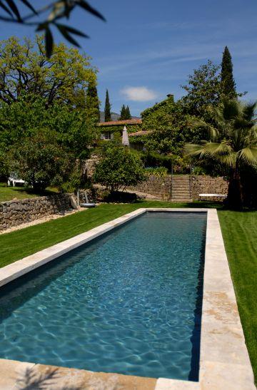Avec quelques dalles rappelant la margelles en pierre, ce bassin de nage traditionnel est d'une élégance rare et donne la sensation d'un tableau aux multiples tonalités de verts.