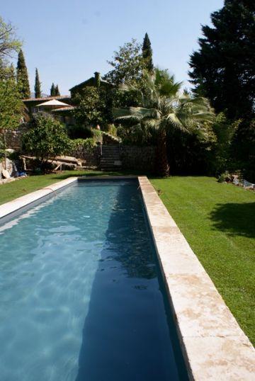 Le bassin de nage est simplement entouré d'une margelle en pierre naturelle. Aucune autre terrasse n'a été ajoutée pour conserver un véritable côté traditionnel à cette piscine.