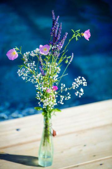 Le décor de cette piscine est simple, presque brut, mais ce petit bouquet de fleurs des champs d'à côté apporte la touche de poésie nécessaire et suffisante pour adoucir l'ensemble.