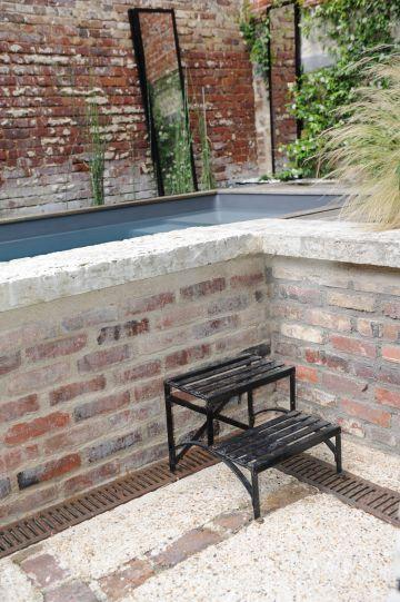 Pour accéder à la piscine, un petit escalier métallique répondant aux poutrelles et IPN de la cour est soigneusement disposé au pied du muret de brique qui ceint la Piscinelle.