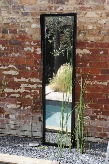 Installé directement contre le mur d'enceinte en brique, un miroir reflète la Piscinelle iki et donne une perspective agréable à l'œil dans cette petite cour intérieure.