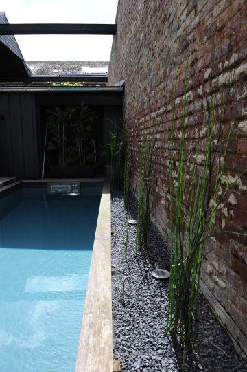 En quelques centimètres, le mur de la piscine, un espace végétalisé avec des bambous et des leds puis directement le mur de clôture... Une réalisation sur-mesure et parfaitement adaptée aux exigences de ce lieu atypique.