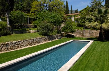 A Cn20 lap pool with stone coping surrounded by a lawn