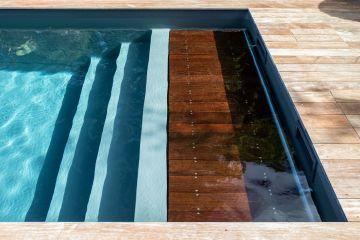 La première marche de l'escalier immergé est également le caillebotis de la couverture automatique de sécurité pour la piscine. Gain de place, discrétion... le luxe se cache dans les détails.