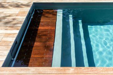 Escamoté sous la première marche de la banquette immergée, le volet de sécurité de la piscine est d'une discrétion égale à son efficacité.