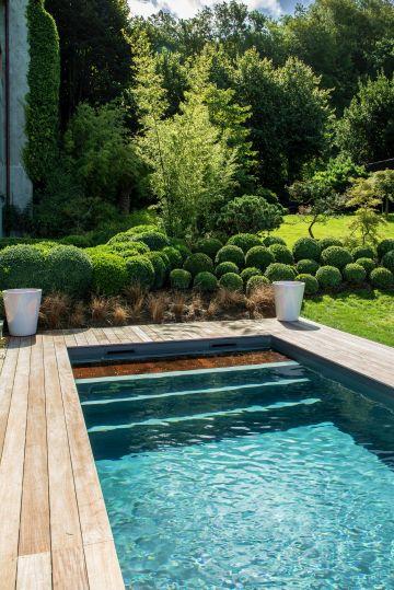 Le massif travaillé en petits buissons ronds tranche avec la netteté des lignes de la piscine. Et le contraste parvient à mettre en valeur aussi bien le paysagisme et la piscine...