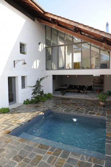 Petite piscine dans une cour intérieur avec abords en pierre naturelle