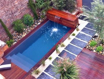 Petite piscine de centre-ville avec des petites margelles en bois