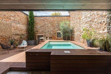 Parfaitement intégré au premier plan, sous la terrasse en bois, est dissimulé le local technique de la piscine. Discret, il fait place à une véritable pièce extérieure tout en déco.