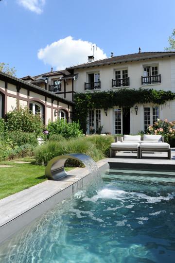 La lame d'eau donne une dynamique à la piscine et une tonalité au jardin...