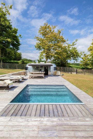 L'espace piscine est tout en variations de gris : l'ipé argenté, la caravane Airstream en inox, le mobilier extérieur et jusqu'au le liner gris ardoise qui donne presque des tons métalliques à l'eau de la piscine.