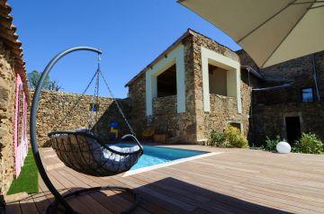 La piscine est surplombé par une terrasse couverte, partie intégrante de cette maison en Ardèche.