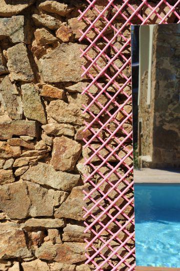 Claustras rose bonbon et miroirs adossés au mur de pierres sèches créent un contraste et apporte une touche déco qui met en valeur la piscine.