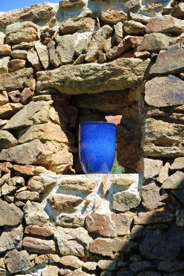 Le petit vase bleu outremer dans la niche du mur crée un point lumineux, un rappel du ciel au-dessus et de l'eau en-dessous.