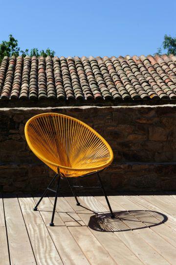 Toujours très déco, l'indémodable fauteuil Acapulco ici dans des tons dorés/orangé, apporte une modernité intemporelle.