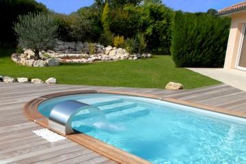 Une piscine arrondie avec une terrasse et lame d'eau
