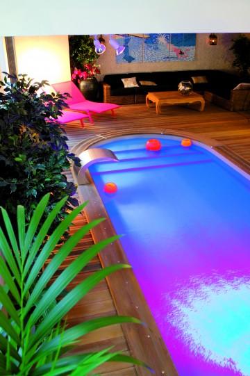 Une piscine arrondie en intérieur avec des éclairages de piscine
