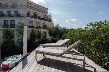 Depuis la terrasse en ipé au bord de la piscine les bain de soleil donnent une vue sur les immeubles environnant pour composer un décors surréaliste.