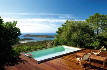 Une piscine rectangulaire Cr6 avec une terrasse devant une vue imprenable sur la baie