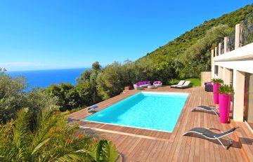 une piscine rectangulaire Cr 10 avec une grande terrasse devant une belle vue en Cote d'Azur