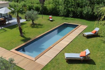 A Cn10 lap pool in the middle of a garden surrounded by a lawn and some wooden decking