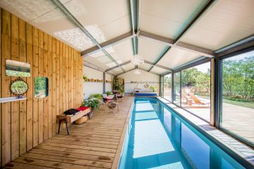 Wide patio doors are positioned along the edge of this extremely well-lit indoor lap pool, opening out onto the Anjou countryside and letting in abundant spring sunshine.