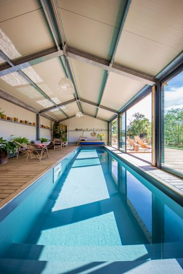 This long indoor lap pool opens up the space and gives new volume to the room.