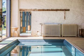 The pool's slate-grey liner contrasts with the colours and aged look of the wall and decorative items.