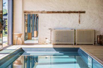 Le liner gris ardoise de la piscine contraste avec les tons et l'aspect ancien du mur et des éléments de décors.
