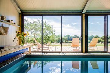 Les larges bais vitrées alignées le long de la piscine sont comme autant de tableaux montrant la campagne angevine. Depuis les canapés à l'intérieur, la piscine se transforme en miroir hypnotique appelant le visiteur de ce gîte à la contemplation.