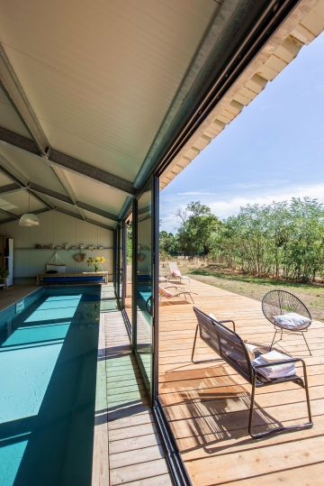 In and out. Une fois les bais vitrées ouverte, cette piscine semble à la fois être une piscine d'intérieur et d'extérieur grâce au prolongement de la terrasse réalisée dans les mêmes matériaux.
