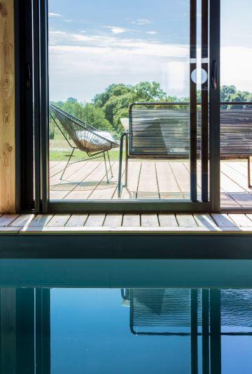Comme un tableau, les lignes verticales et horizontales se croisent et se reflètent sur le plan d'eau de la piscine.
