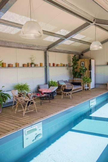 Le même esprit que dans le salon attenant règne dans la salle de la piscine : à la fois déco et simple, quelques meubles en rotin et des coussins qui permettent au visiteur de se sentir loin.