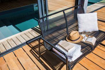 Sous le soleil, au bord de l'eau, avec un livre, des lunettes et un chapeau... le plaisir simple et contigu d'une piscine Piscinelle.