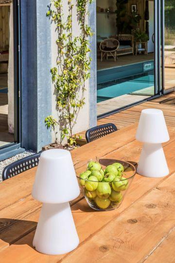 Sur une grande table en bois des lampes d'extérieur et quelques fruits frais pour passer un après-midi et une soirée en été au bord de la piscine.