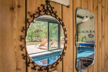 Tout en jeux de reflets, l'accrochage de miroirs anciens séduit par sa simplicité et renvoie aux reflets voisins de la piscine comme ceux d'un miroir d'eau andalouse.