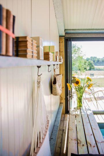 Quelques détails soignés et simples comme de vieux livres, un panier tressé et un bouquet de tournesols sont le décors de cette piscine en pays angevin.