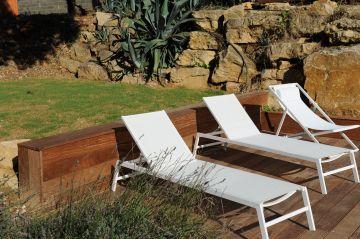 Quelques bains de soleil attendent calmement que les baigneurs viennent se détendre après la natation dans la piscine.