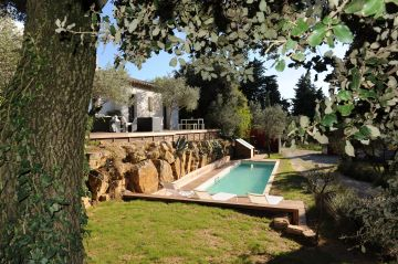 Cette piscine de charme trouve sa place au milieu d'une belle végétation de chênes et d'oliviers.
