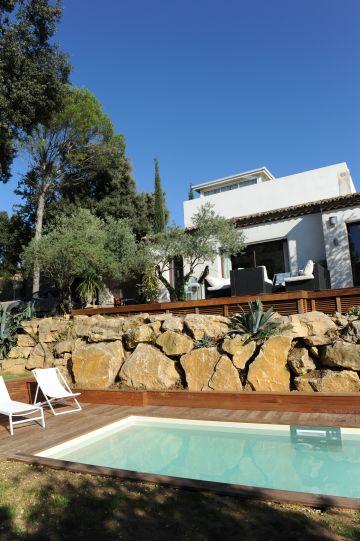 Une piscine de charme au pied d'un maison d'architecte et d'un bel enrochement naturel.