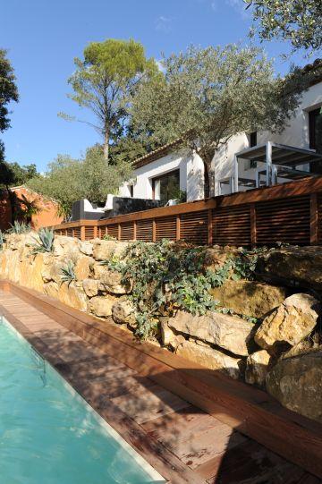 La maison d'architecte toute blanche et rythmée par les larges baies vitrée surplombe la piscine.