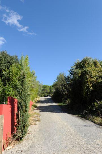 La propriété est ceinte d'un grand mur ocre rouge et borde une petite route provençale.