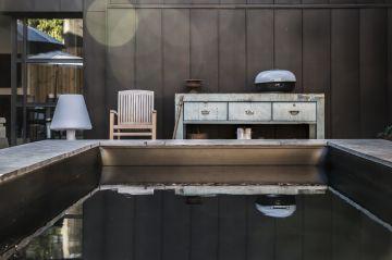 Comme s'ajoutant au mobilier extérieur, la piscine a été conçue dans ce projet comme un meuble design. Loin des clichés, elle est volontairement semi enterrée et drapée d'un liner noir à l'effet déroutant.