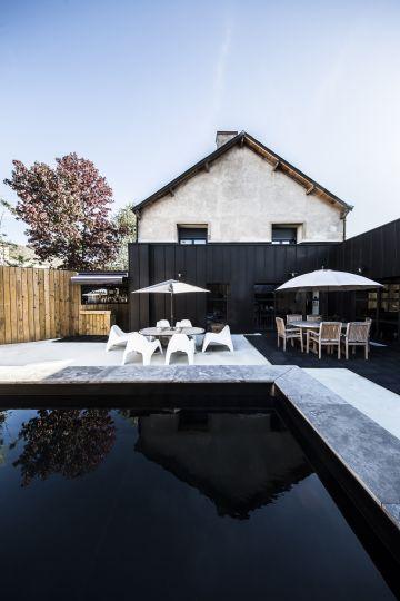 La piscine au premier plan disparaît presque sous l'effet du liner noir qui semble correspondre avec le bardage métallique de la maison moderne.