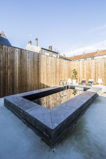 Le liner noir de la piscine agit comme un miroir qui reflète l'ensemble du décor environnent.