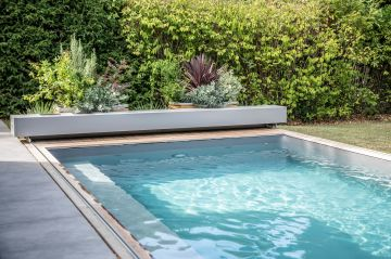 La piscine fait comme une passerelle liquide entre la terrasse en céramique et le gazon du jardin.