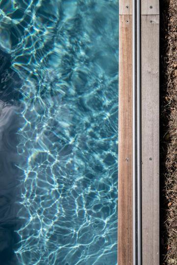 Le rail qui permet de dérouler le Coverseal® est fixé sur la margelle en bois de la piscine.